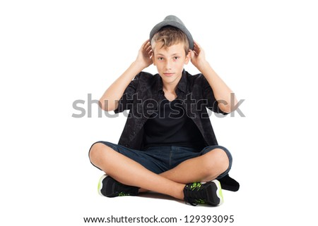 Portrait of a cute young European guy. The guy wearing fashionable clothes and hat sitting on the floor. He holds his hand on his hat. Studio shot, isolated on white background. - stock photo