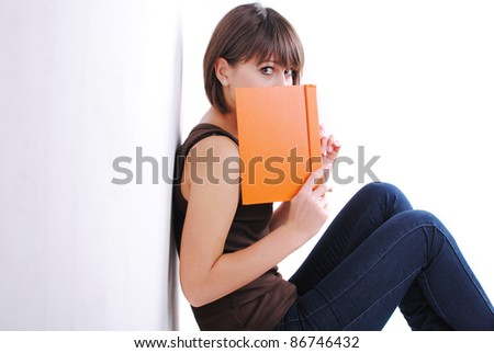 Portrait of a cute young female sitting by the wall reading a book