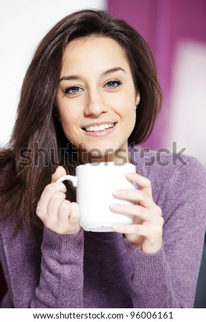 Portrait of a cute young lady with a cup of coffee - stock photo