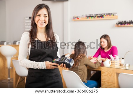 Portrait of a cute young Latin woman holding a credit card terminal at a nail salon and smiling - stock photo