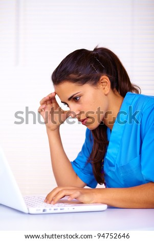 Portrait of a cute young nurse using a laptop.