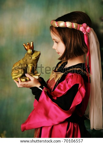 Portrait of a cute young preschool girl dressed as a princess in a pink and gold gown, posing and kissing a frog prince wearing a crown - stock photo