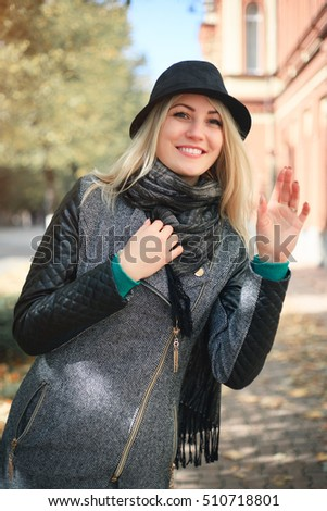 Portrait of a cute young woman in a hat on the street in autumn