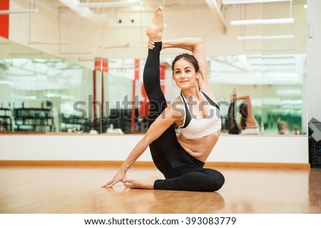 Portrait of a cute young woman stretching and practicing some gymnastic moves at the gym - stock photo