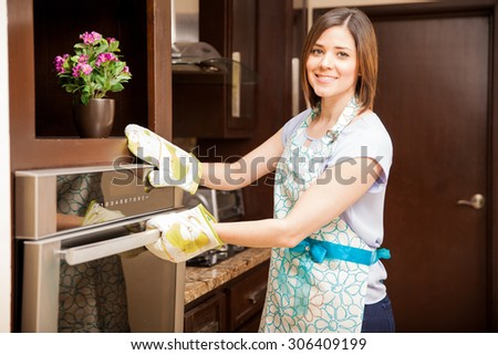 Portrait of a cute young woman wearing an apron and oven mitts opening the oven door - stock photo
