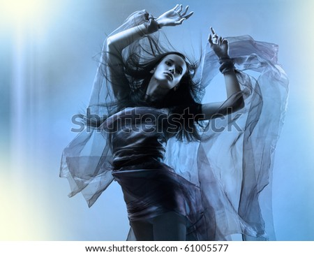 Portrait of a dancing sexy young woman with flying hair and fabric - stock photo