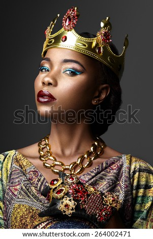 Portrait of a dark-skinned girl in a crown on a gray background