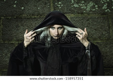 Portrait of a dark witch against a stone background. Halloween and horror.