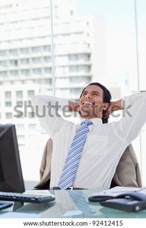 Portrait of a delighted businessman relaxing in his office - stock photo