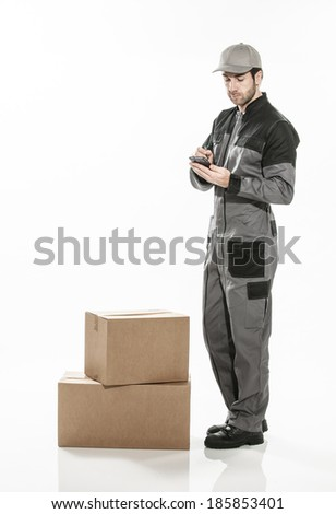 Portrait of a delivery man on isolated background using digital device - stock photo