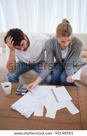 Portrait of a depressed couple doing their accounting in their living room - stock photo