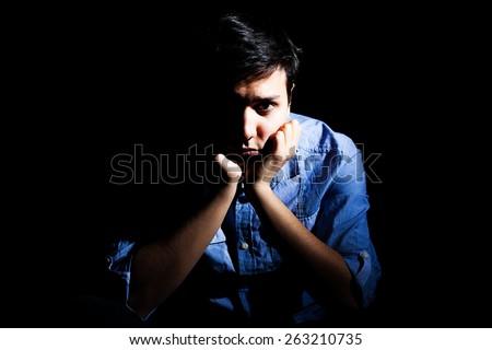 Portrait of a depressed man, black background - stock photo