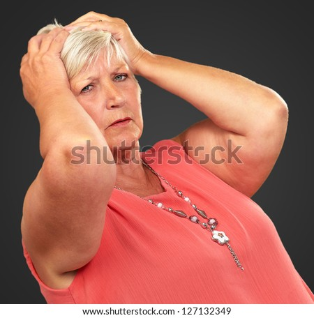 Portrait Of A Depressed Senior Woman On A Black Background - stock photo