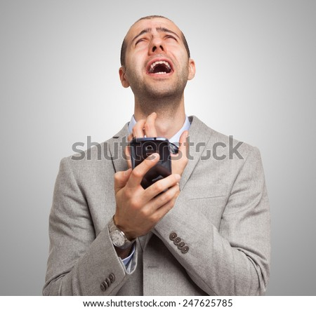 Portrait of a desperate man holding his mobile phone - stock photo