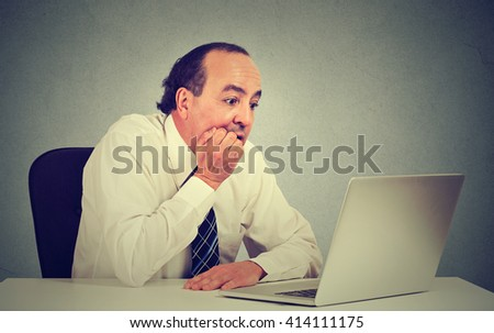 Portrait of a desperate middle aged employee man working on computer in his office isolated on gray wall background. Human face expressions emotions   - stock photo