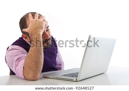 Portrait of a desperate young man looking at laptop against white background. - stock photo