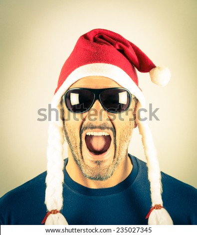 Portrait of a desperate young man with Santa Claus red and sunglasses - Concept of crazy Christmas addiction and shopping holiday lifestyle  - stock photo