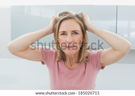 Portrait of a displeased woman pulling her hair - stock photo