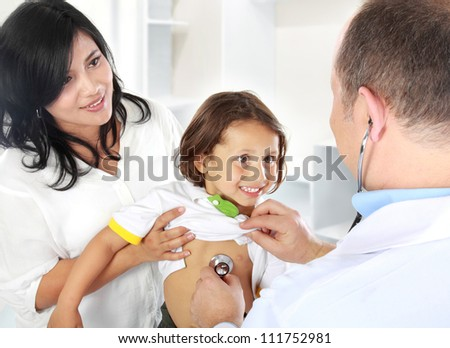 Portrait of a doctor examining heartbeat of the kid with stethoscope - stock photo