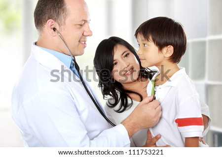 Portrait of a doctor examining youthful patient with stethoscope - stock photo