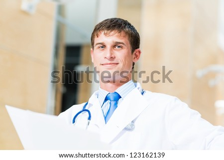 Portrait of a doctor holding papers in hand, office space