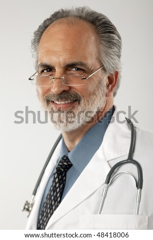 Portrait of a doctor wearing glasses and a white lab coat, with a stethoscope draped around his neck.  He is looking at the camera and smiling. Vertical format. - stock photo