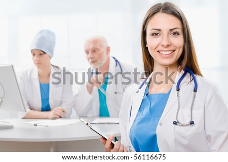 Portrait of a doctor with two of her co-workers sitting  in the background - stock photo