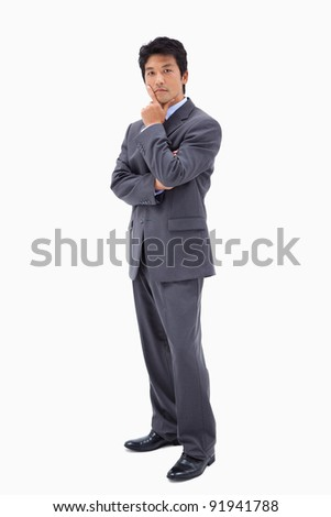 Portrait of a doubtful businessman with the arms crossed against a white background - stock photo