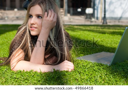 Portrait of a dreaming blond girl with a laptop lying on the grass