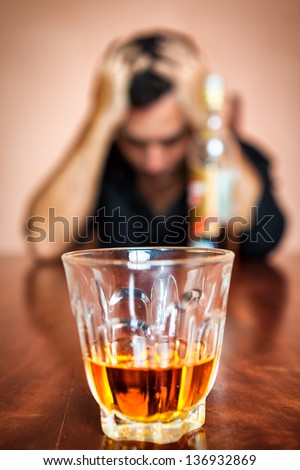 Portrait of a drunk and depressed man addicted to alcohol (Focused on the drink, his face is out of focus) - stock photo