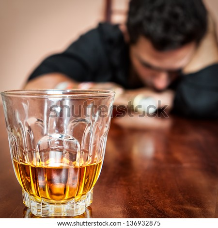 Portrait of a drunk  man addicted to alcohol sleeping with his head on the table  (Focused on the drink, his face is out of focus) - stock photo