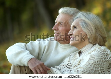 portrait of a elderly couple sitting in autumn park - stock photo