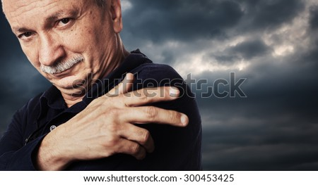 Portrait of a elderly man against dramatic cloudy sky background.  High-contrast image with intentional color shift - stock photo