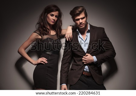 Portrait of a elegant couple leaning on a dark grey wall, the woman wearing a black dress is leaning on the man while the man is unbuttoning his jacket. - stock photo