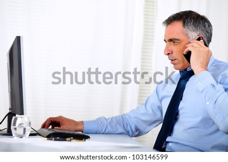 Portrait of a elegant executive man conversing on cellphone at the office - stock photo