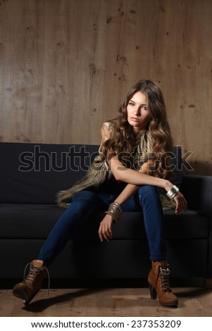 Portrait of a elegant woman sitting on a black sofa wearing a blue jeans and fur vest - stock photo
