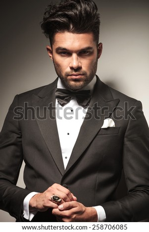 Portrait of a elegant young business man holding his hands together, on grey studio background. - stock photo