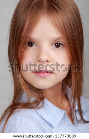 Portrait of a emotional beautiful little girl on gray background