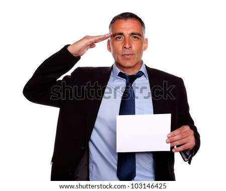 Portrait of a entrepreneur giving a military salute and holding a white card with copyspace against white background - stock photo
