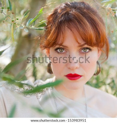 Portrait of a European girl with red hair, green eyes and red lips against the olive branch - stock photo