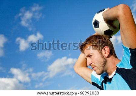 Portrait of a European man holding a football outdoors - stock photo