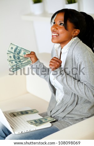 Portrait of a excited afro-american woman looking up with dollars on one hand while is sitting in front a laptop at home indoor - stock photo