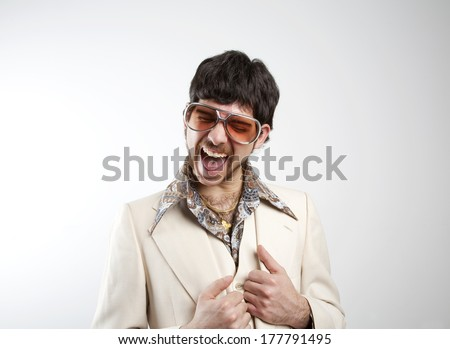 Portrait of a excited retro man in a 1970s leisure suit and sunglasses smiling to the camera  - stock photo