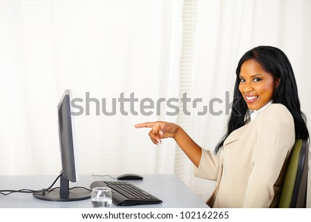Portrait of a executive female pointing the computer screen - stock photo