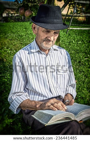 Portrait of a expressive old farmer reading leaning on an apple tree. Close-up portrait. - stock photo