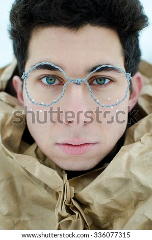 portrait of a fairytale hero  in hand made silver  wire glasses with silver painted freckles and deep blue eyes