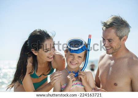 portrait of a family in swimsuit at the beach with the little girl with a diving mask - stock photo