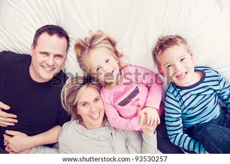 Portrait of a family lying on a bed in their pajamas. - stock photo