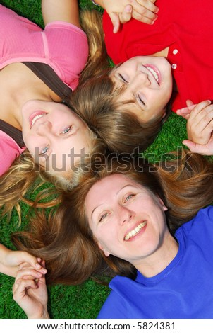 Portrait of a family - mother and children - lying on grass in a park - stock photo