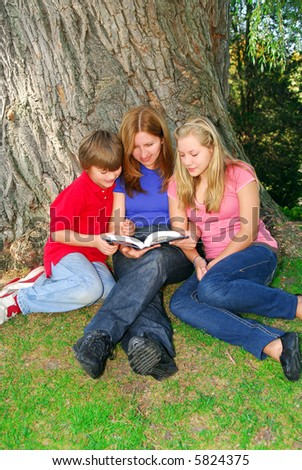 Portrait of a family - mother and children - reading a book in a park - stock photo